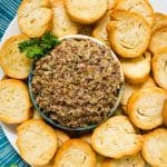 An overhead image of a bowl of Olive Tapenade on a large plate surrounded by toasted sliced baguette