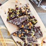 Various varieties of Chocolate bark shards on wooden chopping board