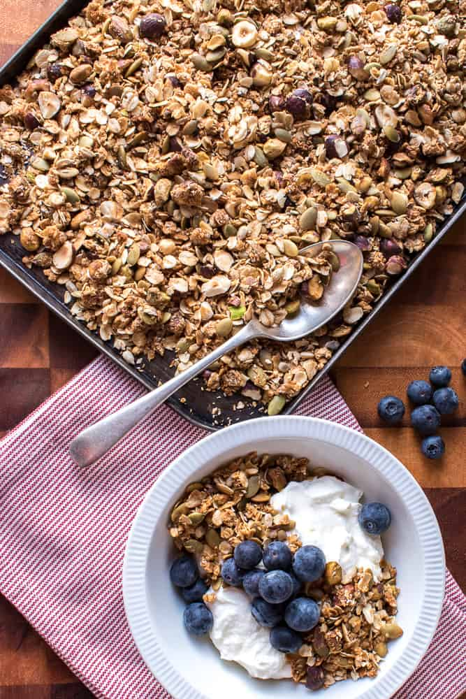 baking tray of homemade granola with white bowl of granola, yogurt and blueberries