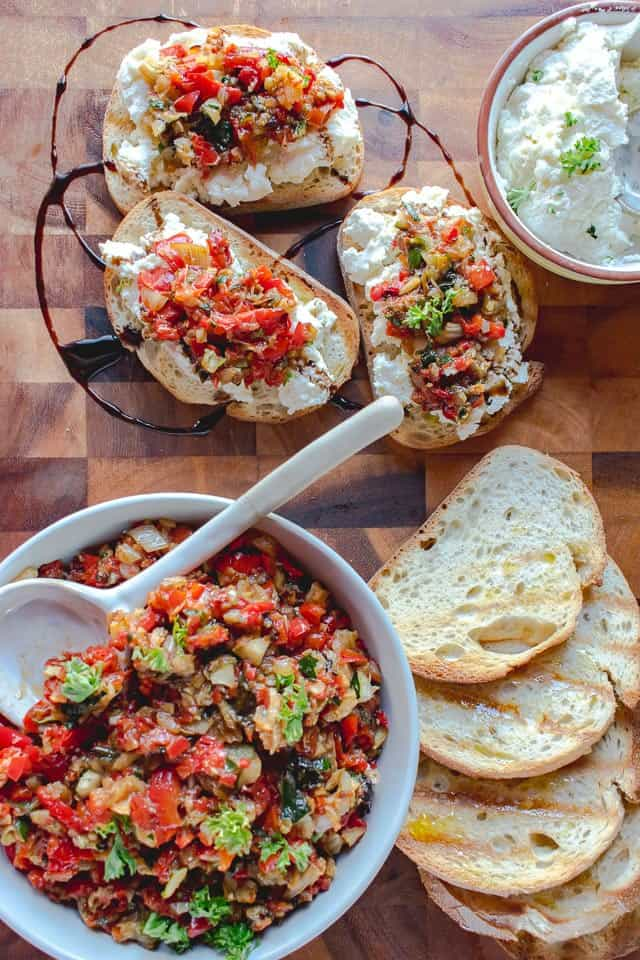 Bowl of roasted vegetable bruschetta, slices of toasted bread, bowl of ricotta, three slices of bread topped with ricotta and roasted vegetable bruschetta
