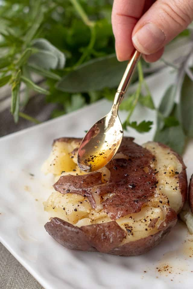a small gold spoon spooning on browned butter onto the smashed potatoes