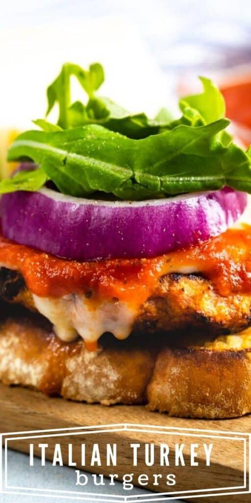 Turkey burgers on garlic bread sitting on a cutting board