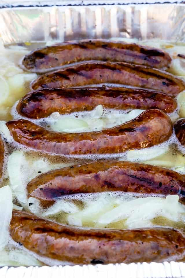 Close up shot of beer brats cooking in a deep metal pan with light beer and onions