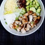 Overhead shot of caesar salad ingredients in a white bowl with recipe title on bottom