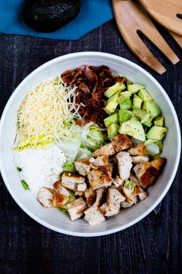 Overhead shot of caesar salad ingredients unmixed in a white bowl on table with salad forks