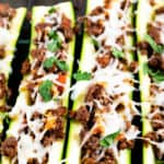 Vertical shot of italian stuffed zucchini boats with herbs in background