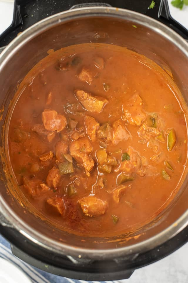 Overhead shot of chicken curry in instant pot being cooked with sauce