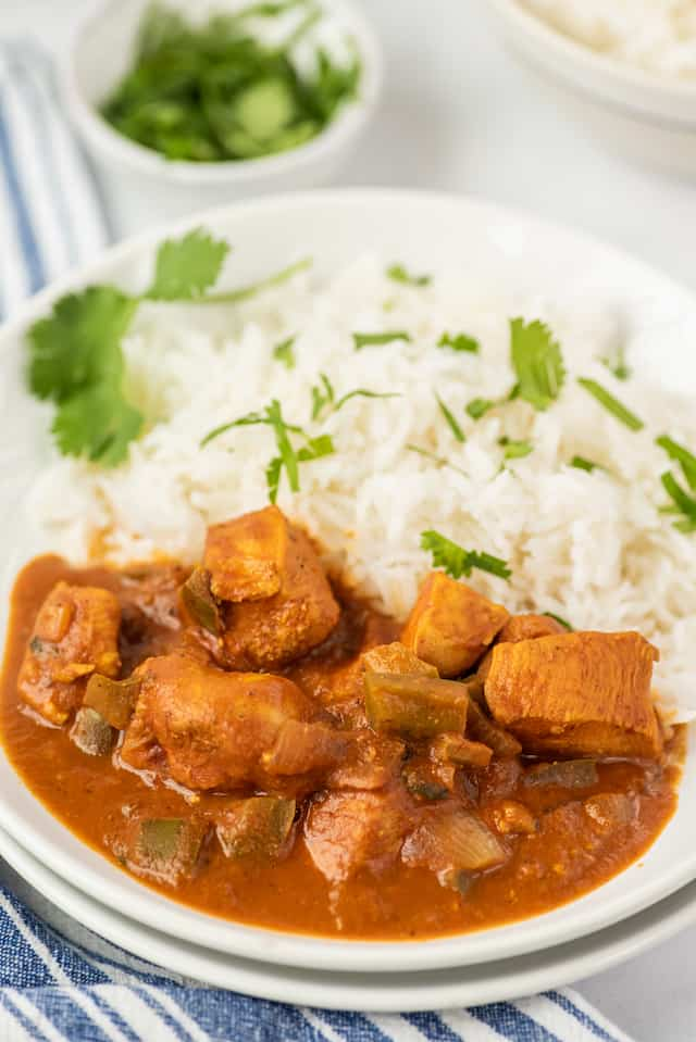Chicken curry and white rice in a white bowl on table with blue and white striped napkin