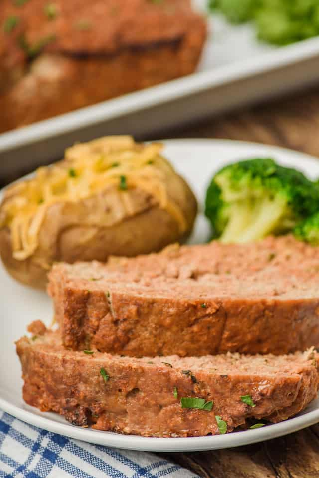 sliced meatloaf on white plate with potato and broccoli