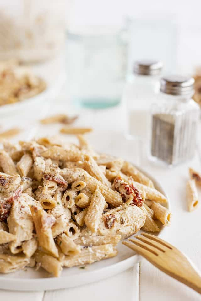 Chicken bacon ranch pasta on a white plate with wood fork