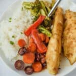 Overhead shot of honey garlic chicken, vegetables and rice on a white plate with fork and recipe title on bottom of image