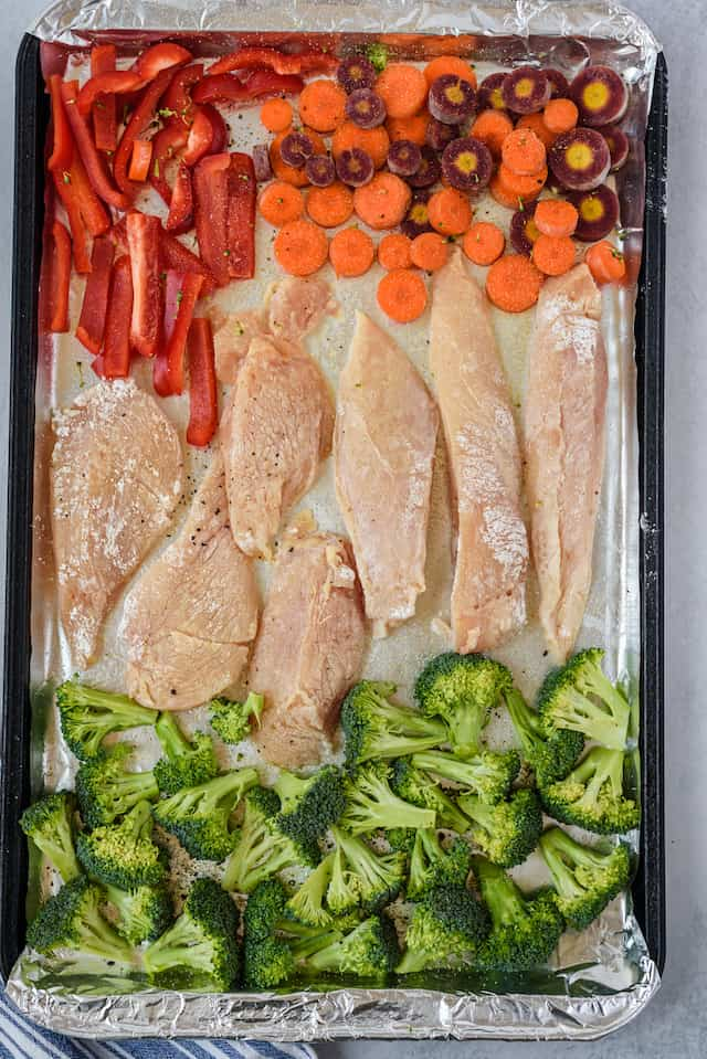 Overhead shot of garlic honey chicken and veggies on a sheet pan not cooked