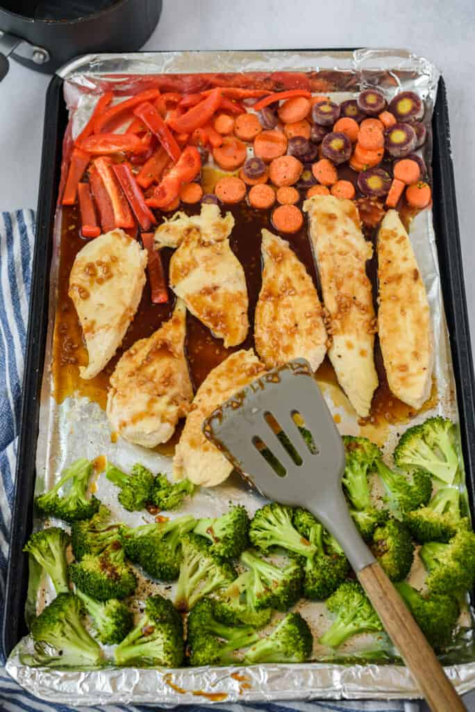 Honey garlic chicken and veggies on a sheet pan with spatula