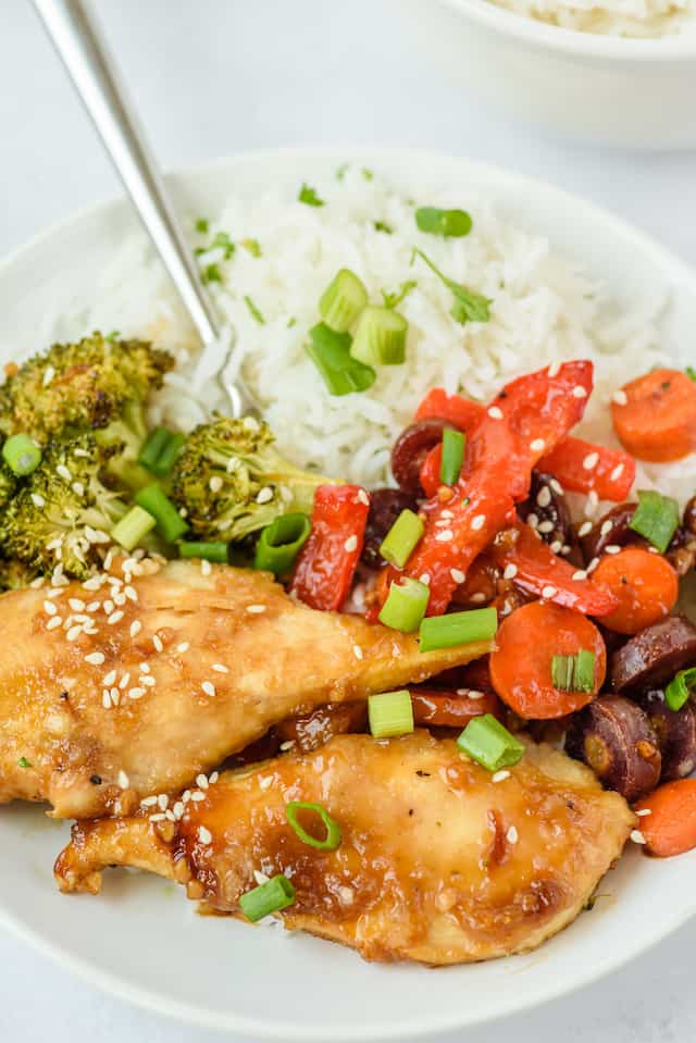 Close up shot of honey garlic chicken, vegetables and rice on a white plate with fork