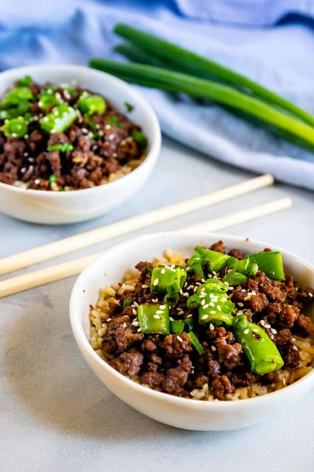 Korean beef bowls in white bowls with chopsticks in between