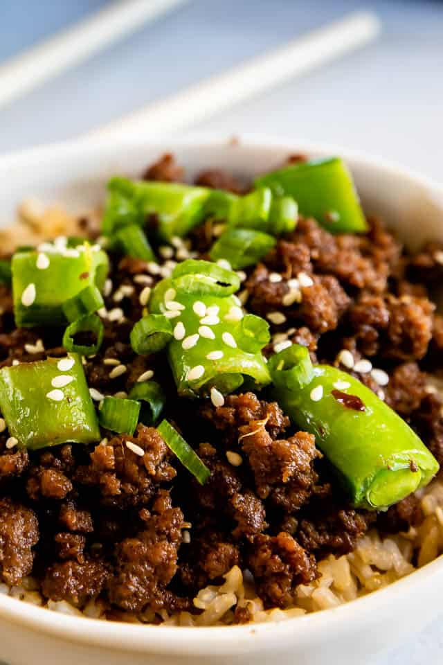 Close up shot of korean beef bowls with green onions and sesame seeds on top