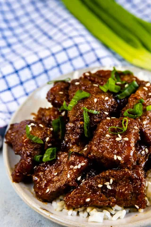 Overhead shot of mongolian beef on a grey plate with white rice and blue checkered napkin and green onions in background