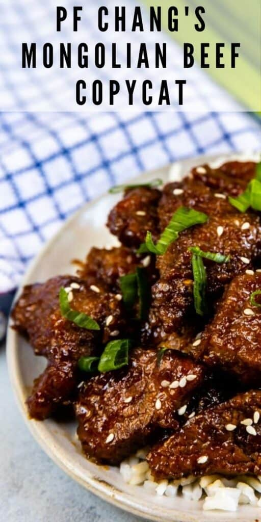 Overhead shot of mongolian beef on a grey plate with white rice and blue checkered napkin and green onions in background and recipe title on top of image