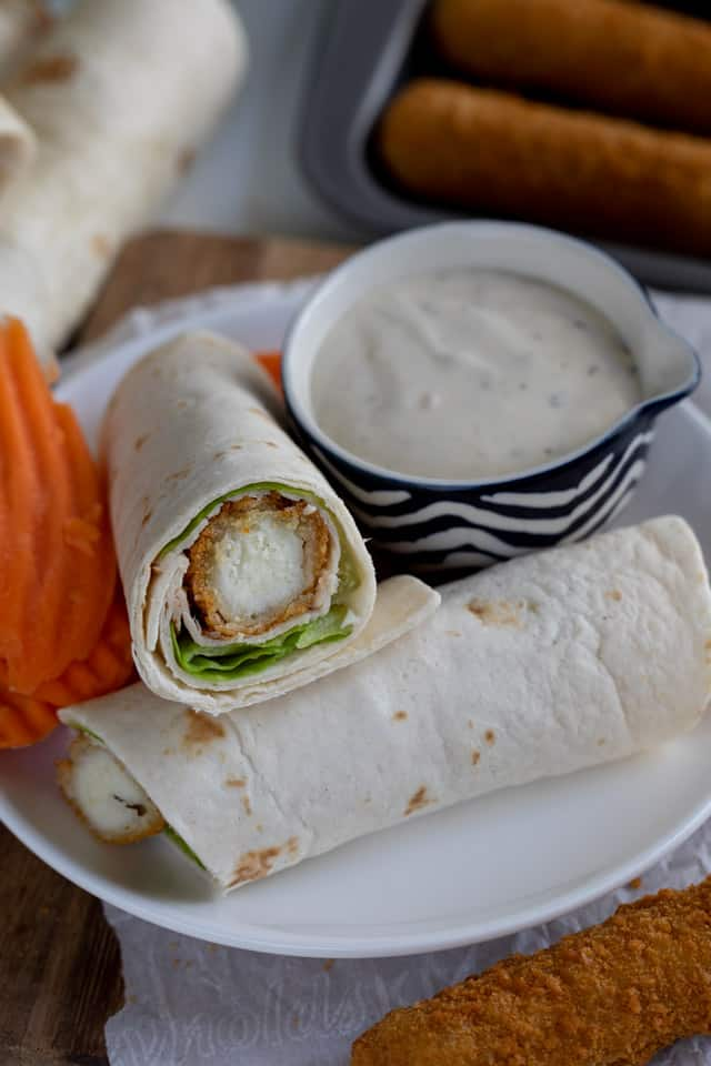 Easy turkey wraps on a white plate with a side of carrots and ranch