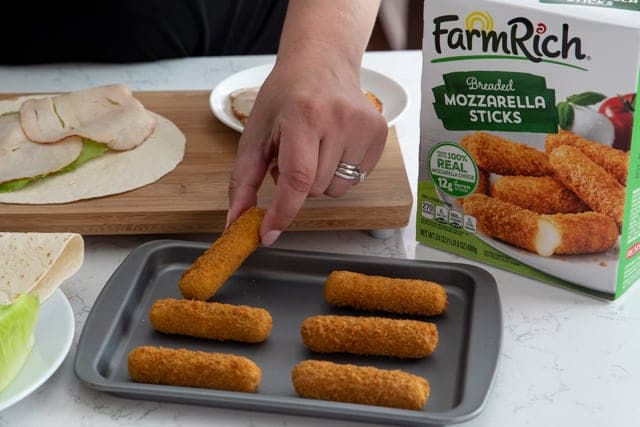 Mozzarella stick on a pan with turkey wrap ingredients behind it