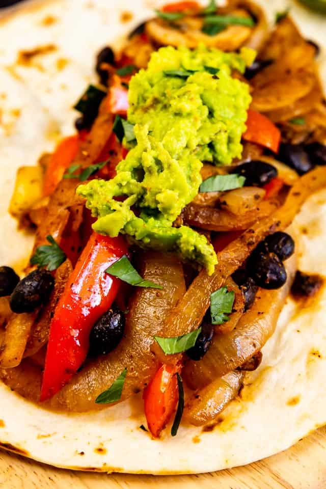 Close up shot of vegetarian fajitas in a tortilla with guacamole on top