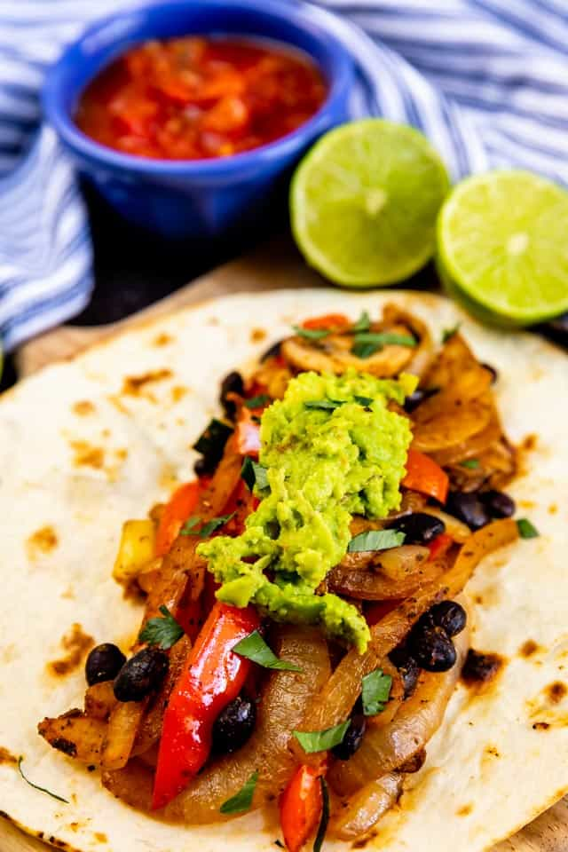 Vegetarian fajita with guacamole on top and salsa and limes in background