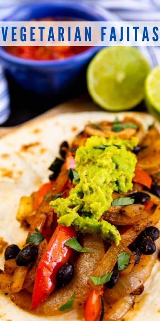 Vegetarian fajita with guacamole on top and salsa and limes in background and recipe title on top