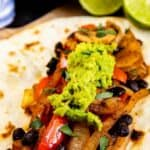 Vegetarian fajita with guacamole on top and salsa and limes in background and recipe title on bottom