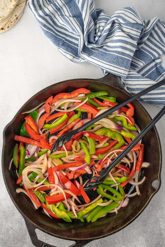 Overhead shot of veggies being cooked in cast iron skillet with tongs