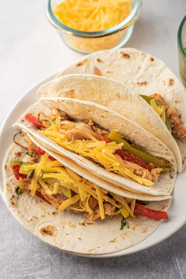 Easy chicken fajitas in tortillas on a white plate with cheese in a dish