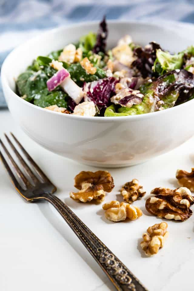 Apple walnut salad in a white bowl with silver fork and walnuts in front of it