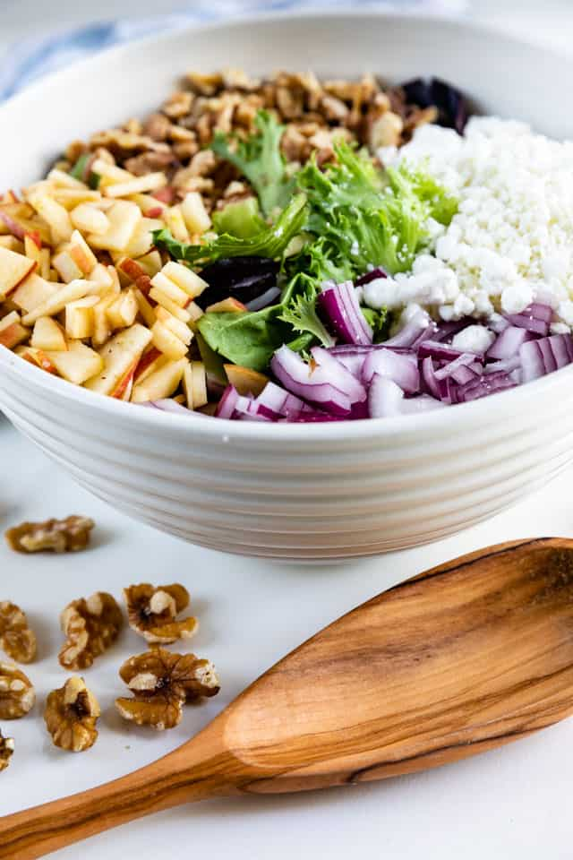 Overhead shot of apple walnut salad ingredients in a white bowl with wooden spoon in front of it