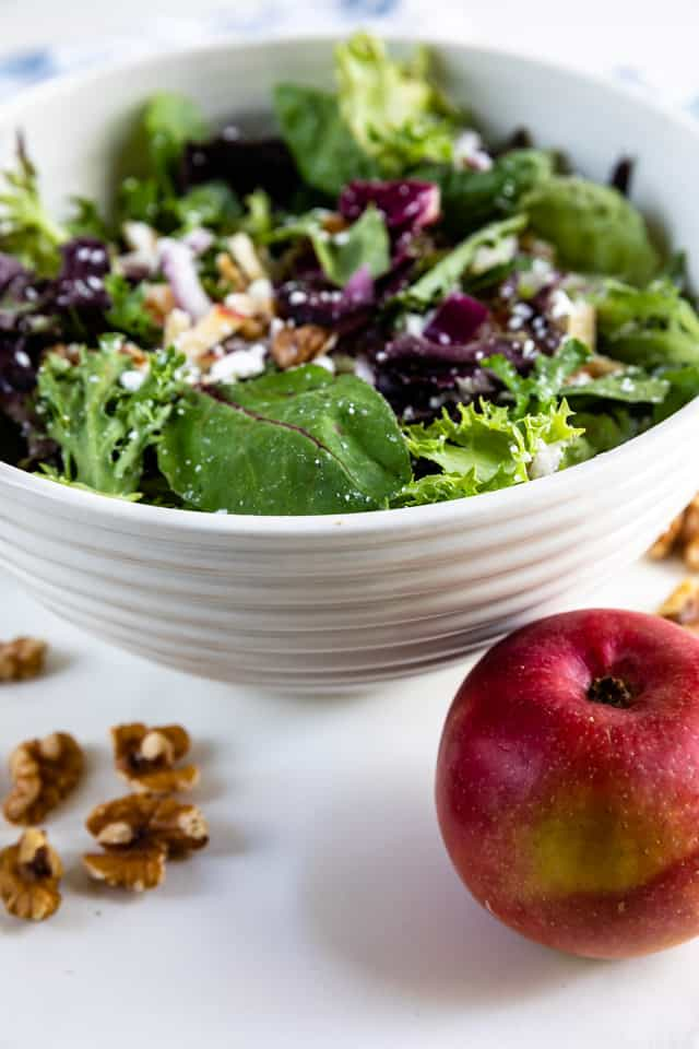 Apple walnut salad in a white bowl with walnuts and apple in front of bowl