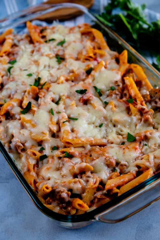 Overhead shot of baked penne and sausage casserole in a clear baking dish