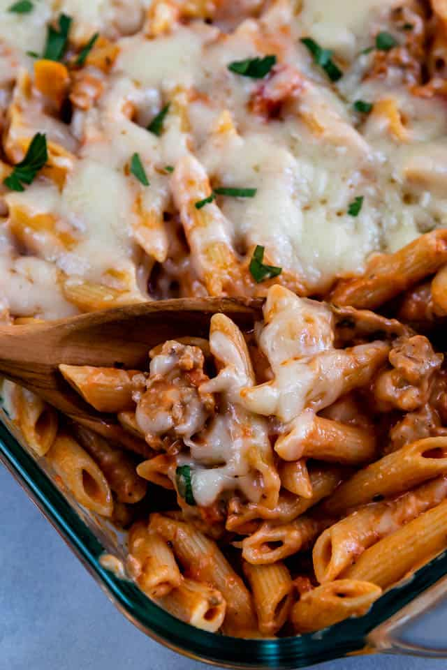 Close up of baked penne and sausage being scooped out of casserole dish with a wooden spoon