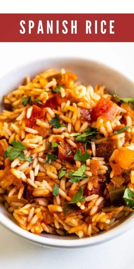 Overhead shot of spanish rice in a white bowl topped with cilantro and recipe title on top