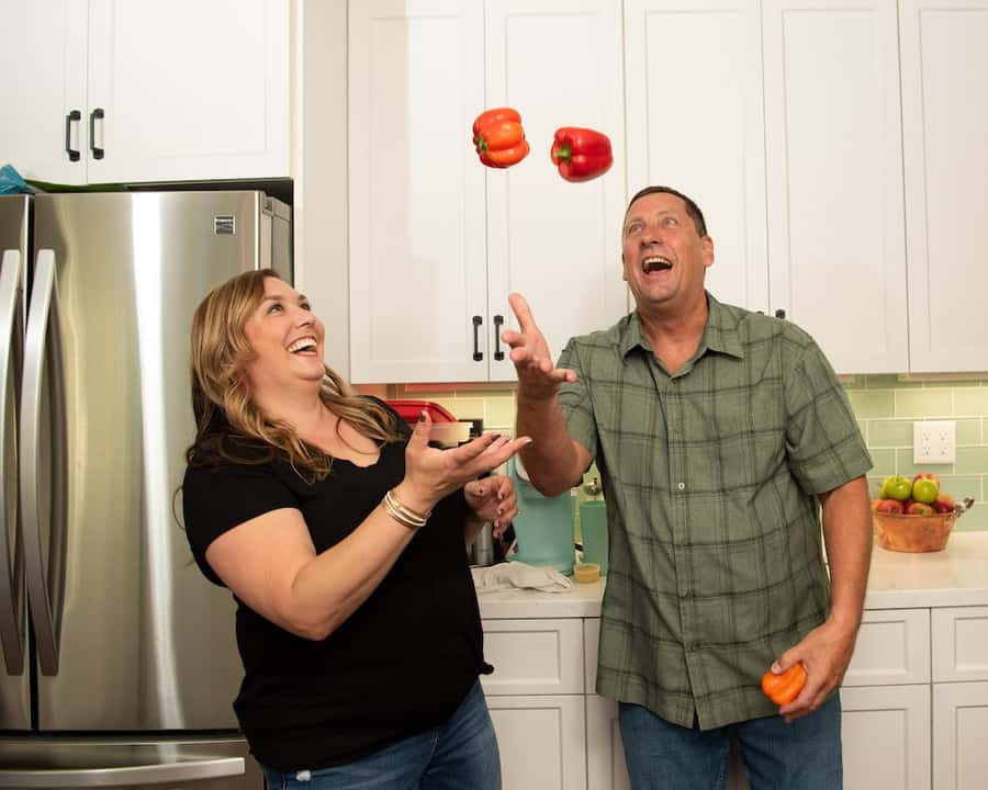 man and woman juggling bell peppers