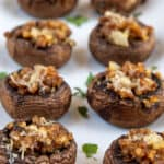 Stuffed mushrooms in two rows on a white serving platter
