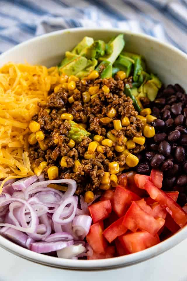 Overhead shot of taco salad ingredients in a bowl in sections not mixed together