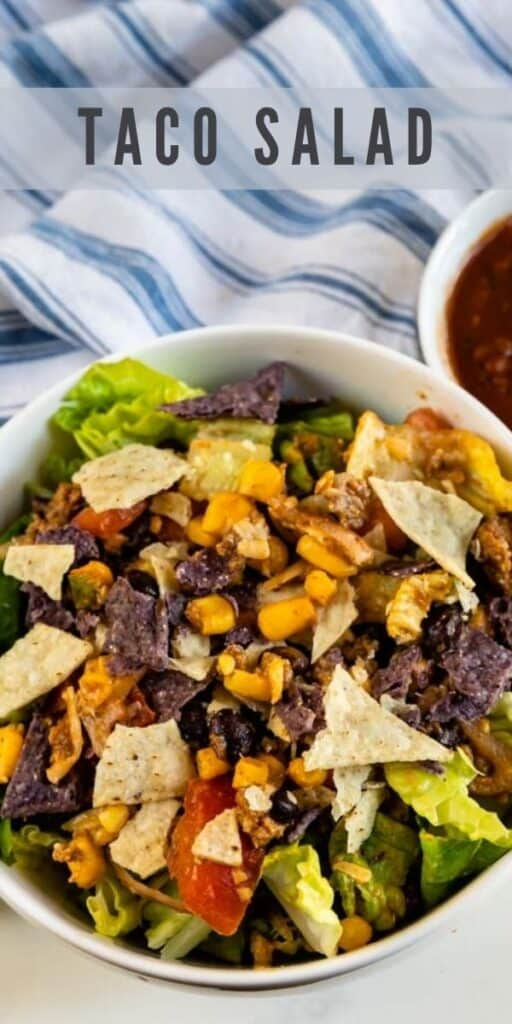 Overhead shot of taco salad in a white bowl on the counter with salsa next to it and recipe title on top of image