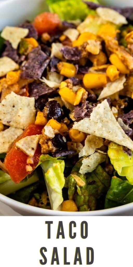 Close up shot of taco salad in a bowl with recipe title on bottom of image