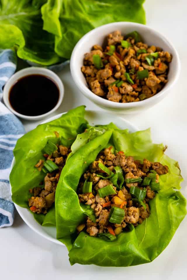 Overhead shot of turkey lettuce wraps on a plate with extra turkey and sauce next to plate