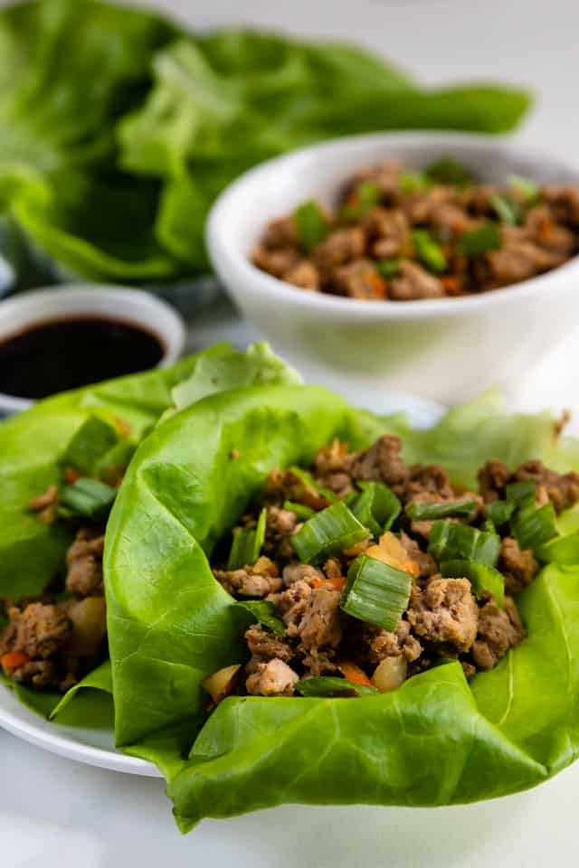 Close up shot of turkey lettuce wraps on a plate with extra ground turkey and sauce in background