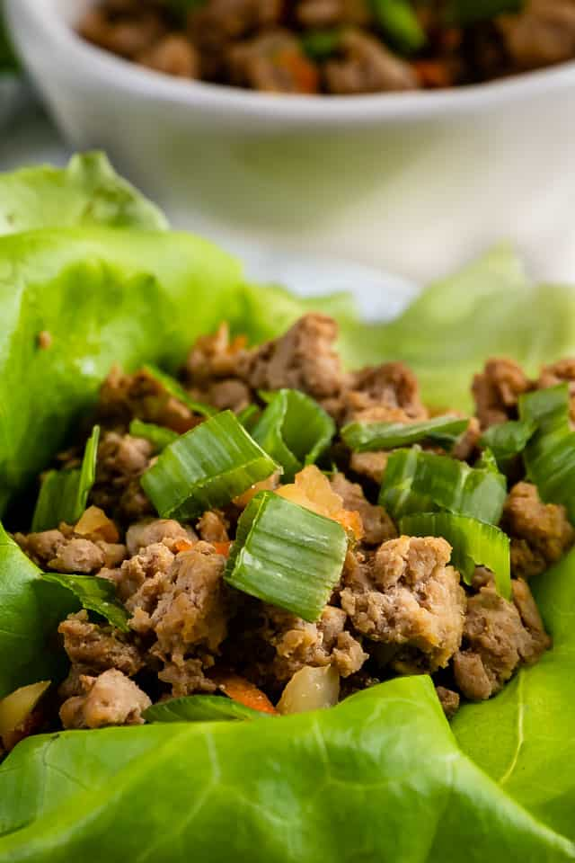Close up of lettuce leaf filled with ground turkey and topped with green onions