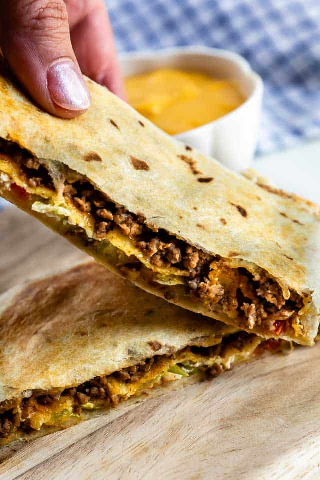 Close up photo of crunchwrap supreme cut in half to show filling
