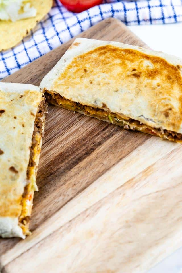 Crunchwrap supreme is cut in half on a wood cutting board