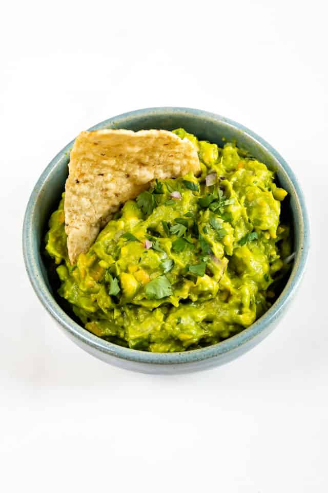 Overhead shot of a bowl of easy guacamole with one tortilla chip in the dip