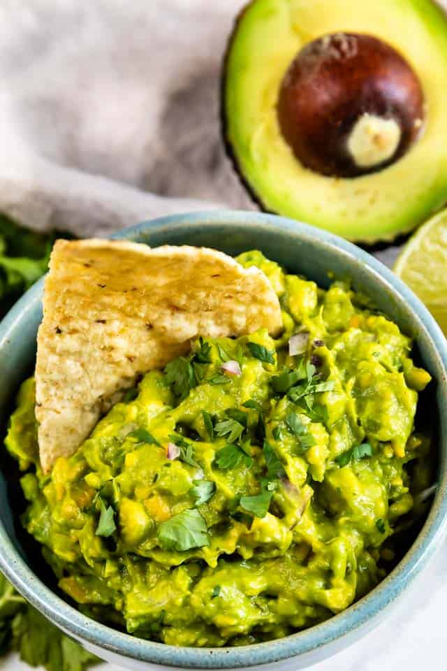 Close up overhead shot of a bowl of easy guacamole with one tortilla chip in the dip