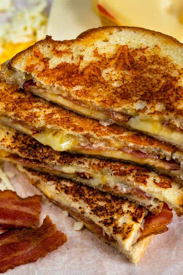Grilled cheese sandwiches cut in half and stacked on top of eachother surrounded by cheese and bacon