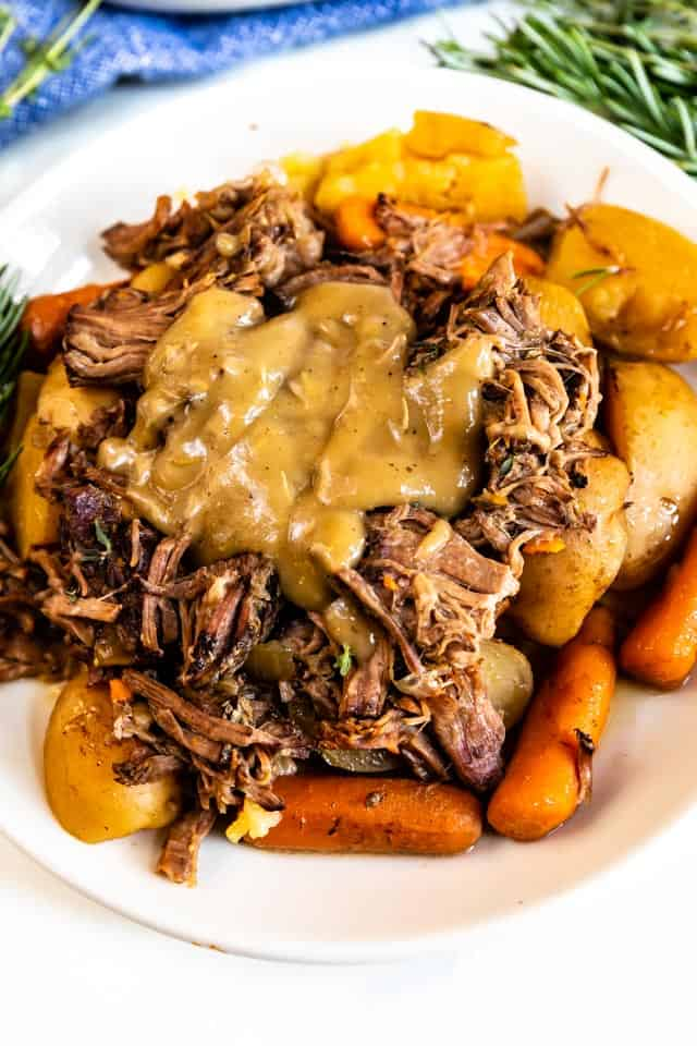 Pot roast on a white plate with brown gravy on top